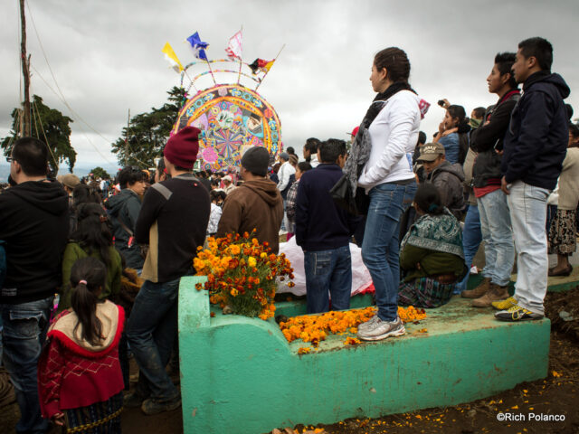 people climing over graves at Santiago Sacatepequez guatemala
